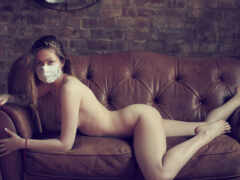 голая девушка в маске на диване