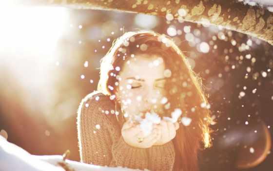 девушка сдувает снег