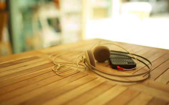 смартфон с наушниками на деревянном столе