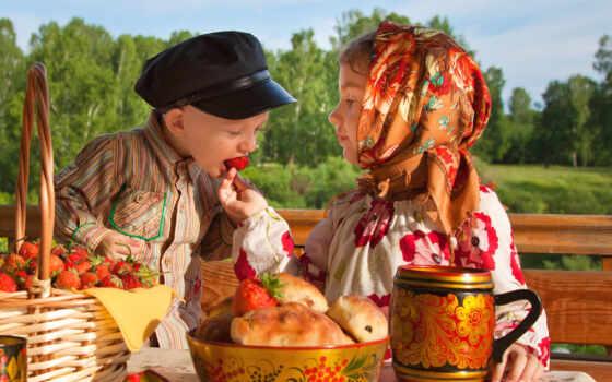 девочка кормит мальчика клубникой