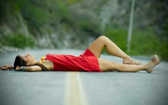 девушка лежит на горной дороге